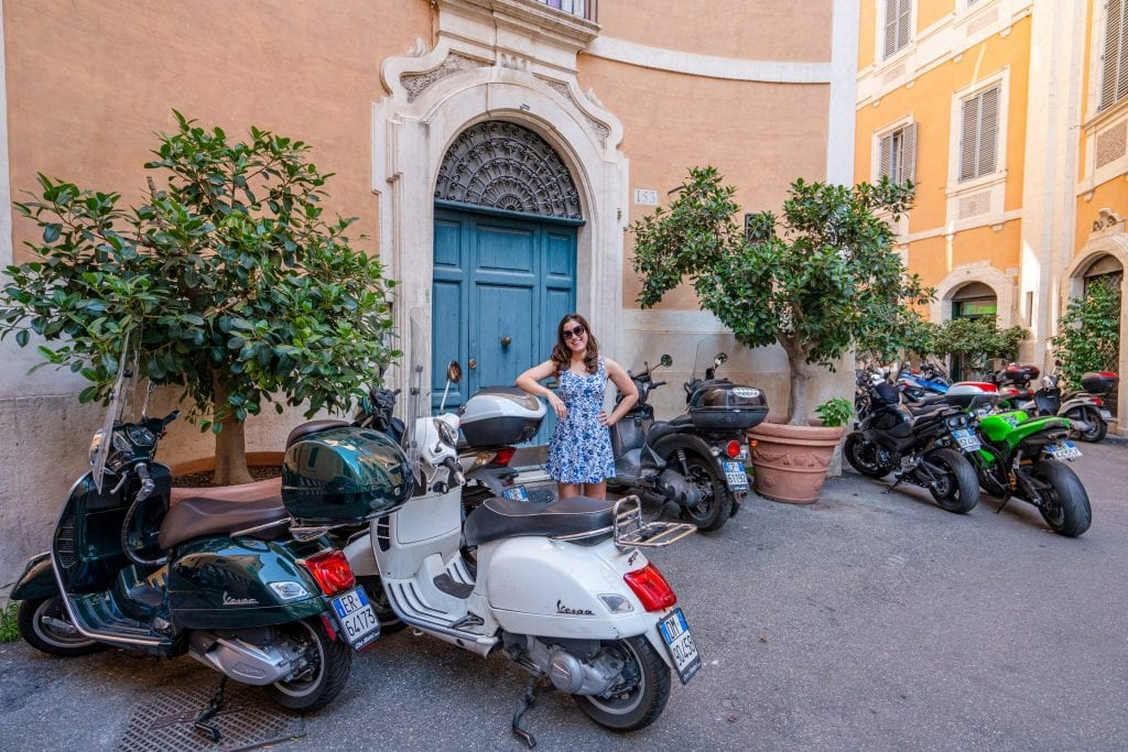 Kate Storm leaning against a Vespa parked in front of a building in Rome Italy--you can learn all kinds of fun facts about Italy when wandering around Rome!