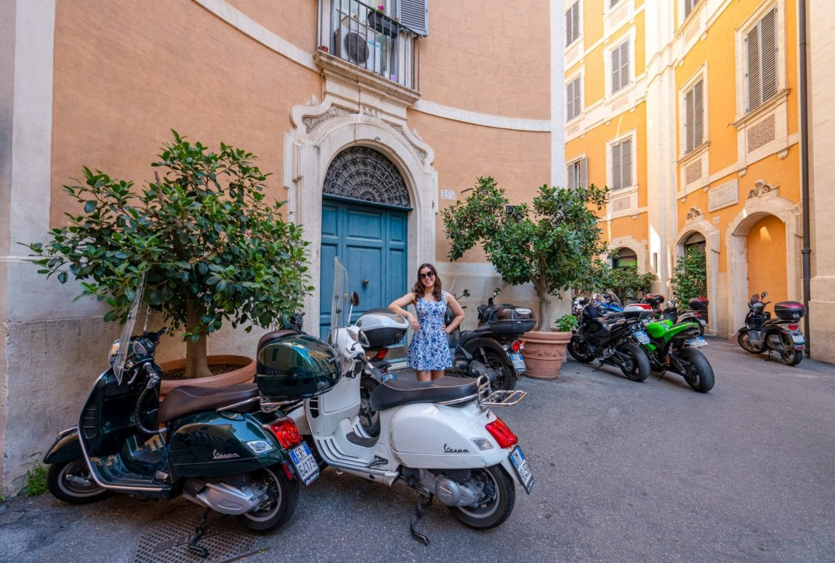 Kate Storm in a blue dress standing next to a Vespa on a street in Rome Italy--you'll see plenty of streets like this during your Rome vacation!