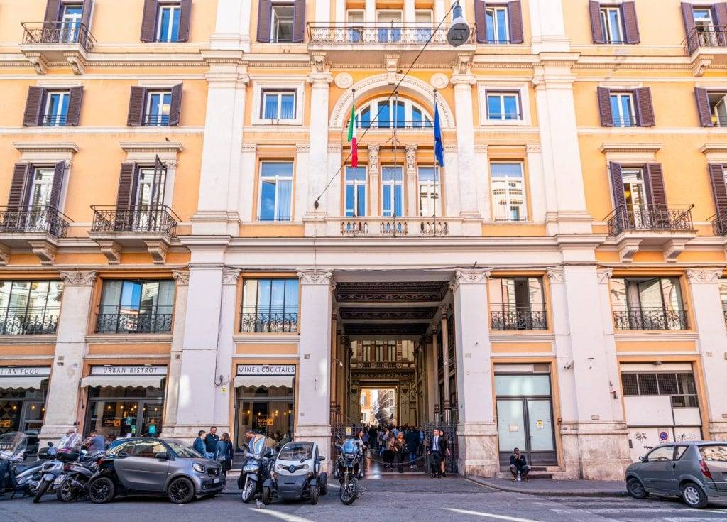 Entrance to the Galleria Sciarra in Rome, showing a yellow building exterior with vespas parked out front