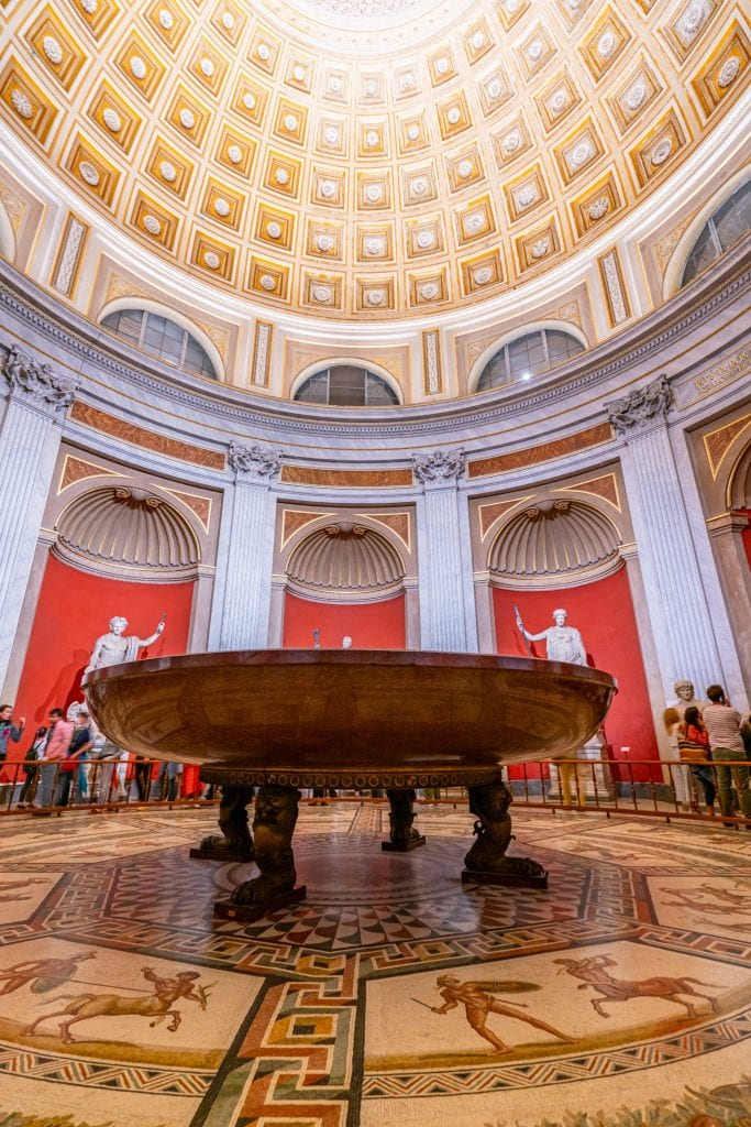 Large basin as seen when visiting the Vatican Museums, housed underneath a dome. Walls in the background are painted red.