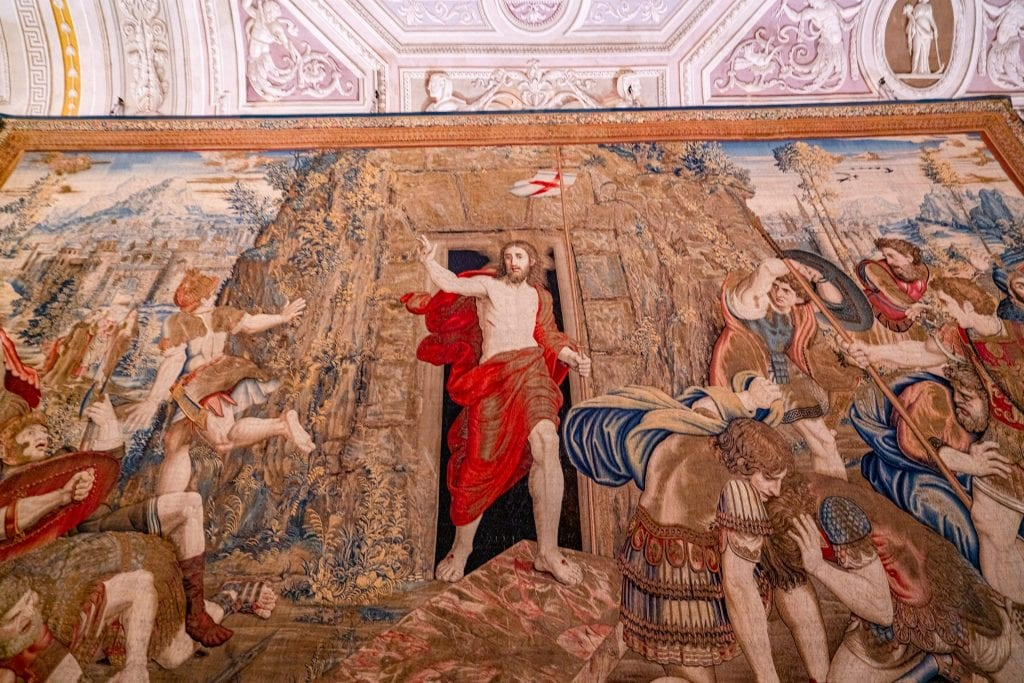 Tapestry with Jesus in the foreground in a red robe, as seen when visiting the Vatican Museums in Rome