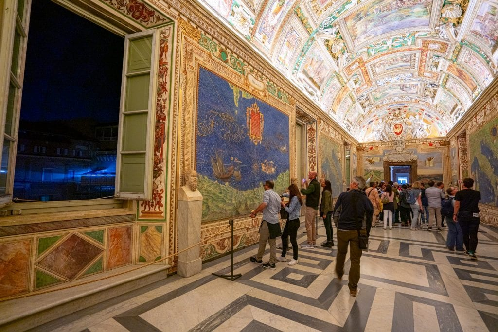 Map room in the Vatican Museums shot at night, with open window on the left. Visiting the Vatican Museums during special hours is one of our favorite travel tips for Rome Italy!