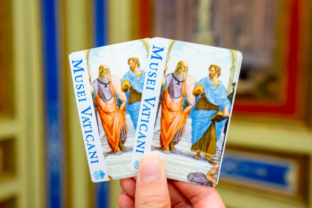 Two tickets for the Vatican Museums being held up in front of a colorful wall--pre-booking these tickets is one of the most important Vatican travel tips