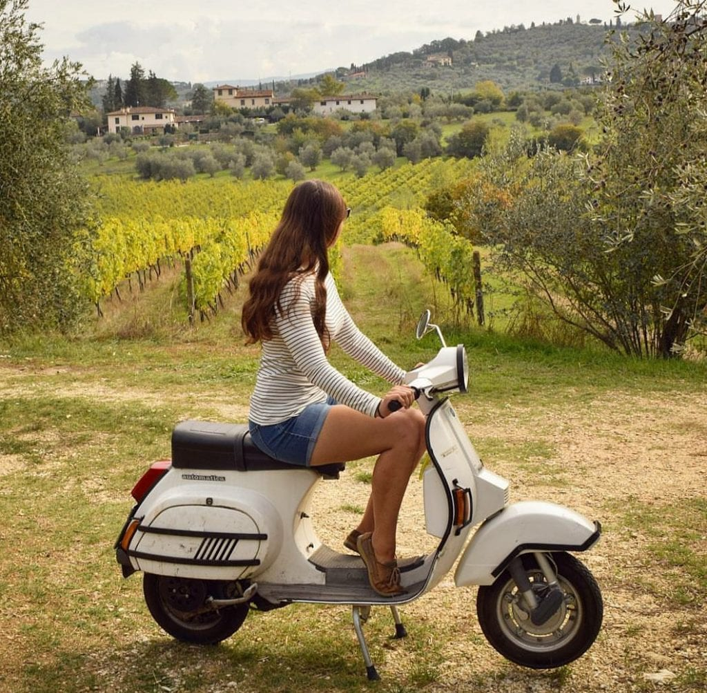 Kate Storm on a white Vespa in the Tuscan countryside--riding a Vespa is an incredibly fun experience during a Tuscany itinerary!