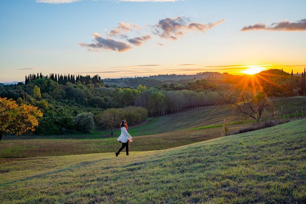 Kate Storm in the Tuscan countryside at sunset, with a sun flare on the right side of the photo.