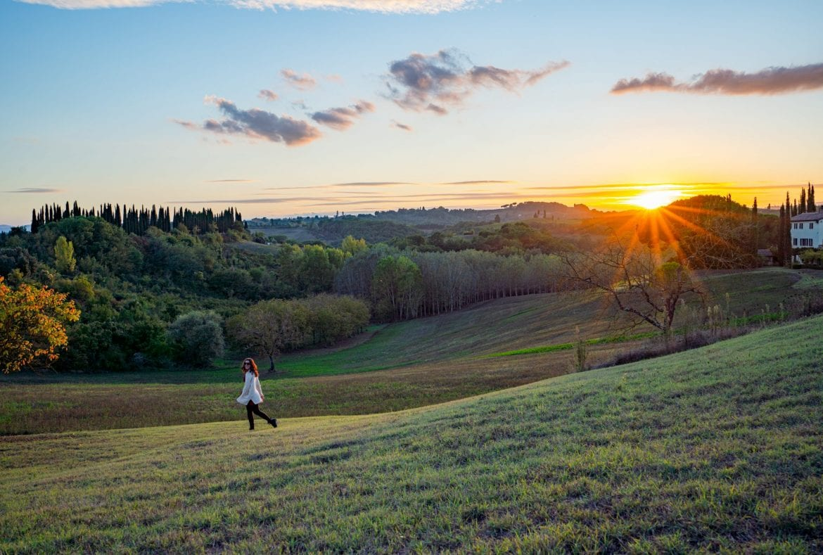 Kate Storm in the Tuscan countryside at sunset with a sun flare on the right side of the photo--Tuscan sunsets are an epic part of any Tuscany road trip itinerary.