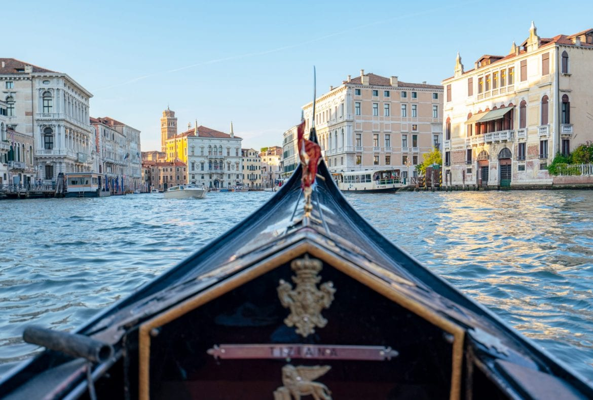 A photo of the front of a Venetian gondola in the foreground with the Grand Canal in the background--the absolute best views of Venice can be found from inside a gondola!