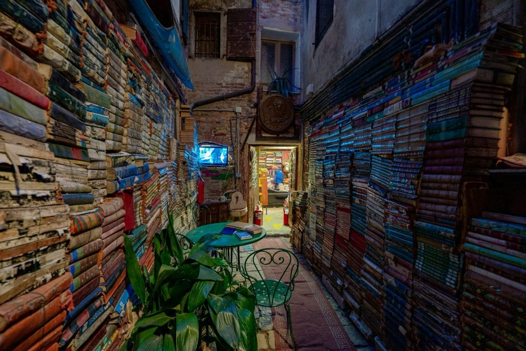 Entrance to Libreria Acqua Alta at night, with books stacked on either side of the walkway