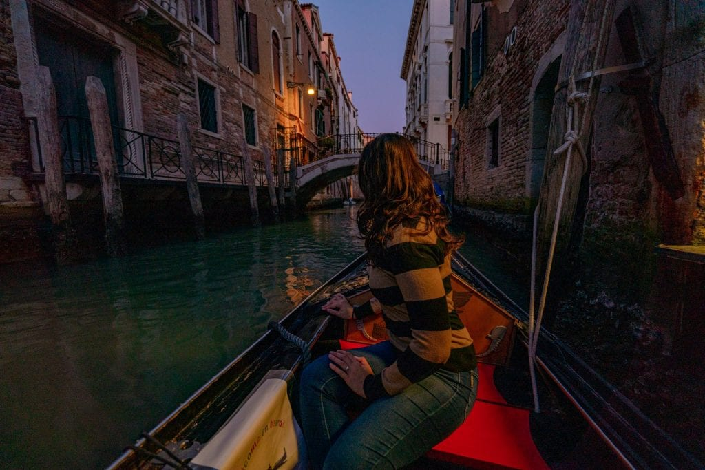 Kate Storm sitting in a gondola at night looking away from the camera. A nighttime gondola ride is one of the best things to do in Venice at night!