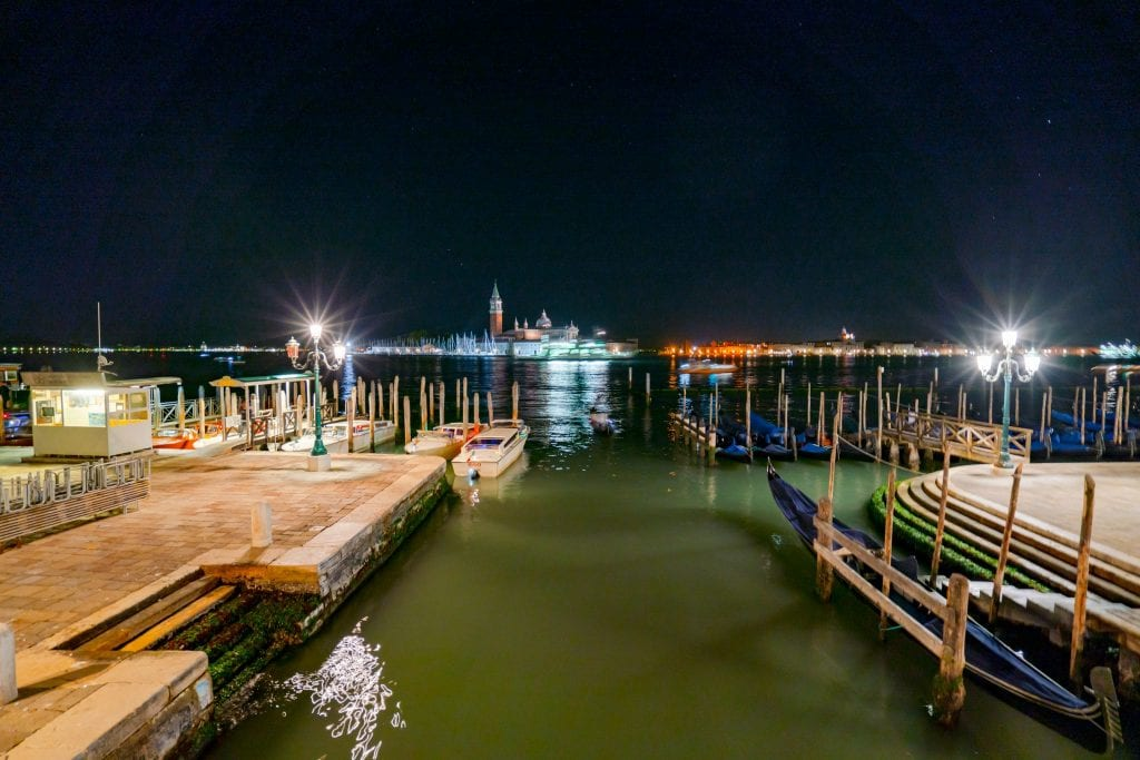 Photo of Venetian Lagoon from Riva degli Schiavoni at night, with parked gondolas visible--when deciding what to do in Venice at night, don't forget about the joy of taking a walk!