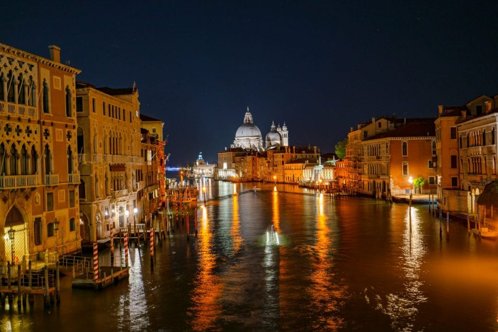 Photo of the Venetian Grand Canal at night with lights reflecting on the water--when deciding what to do in Venice at night, make sure you include seeking out a few views like this.