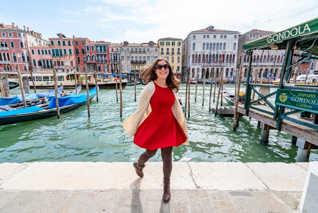 Kate Storm in a red dress spinning in front of the Grand Canal in Venice