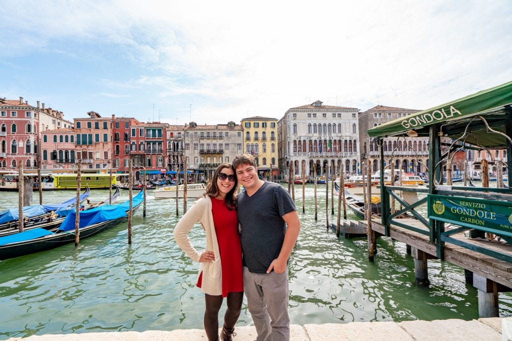 Kate Storm and Jeremy Storm standing along the Grand Canal of Venice. Kate is in a red dress and there are gondolas behind them.