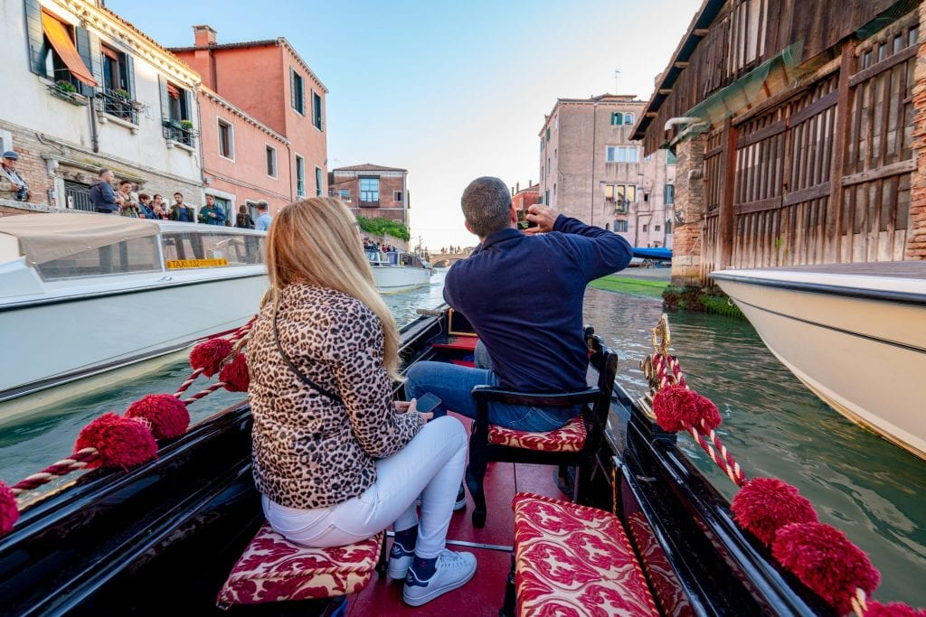 A man and a woman on a gondola ride in Venice, the man is taking photos