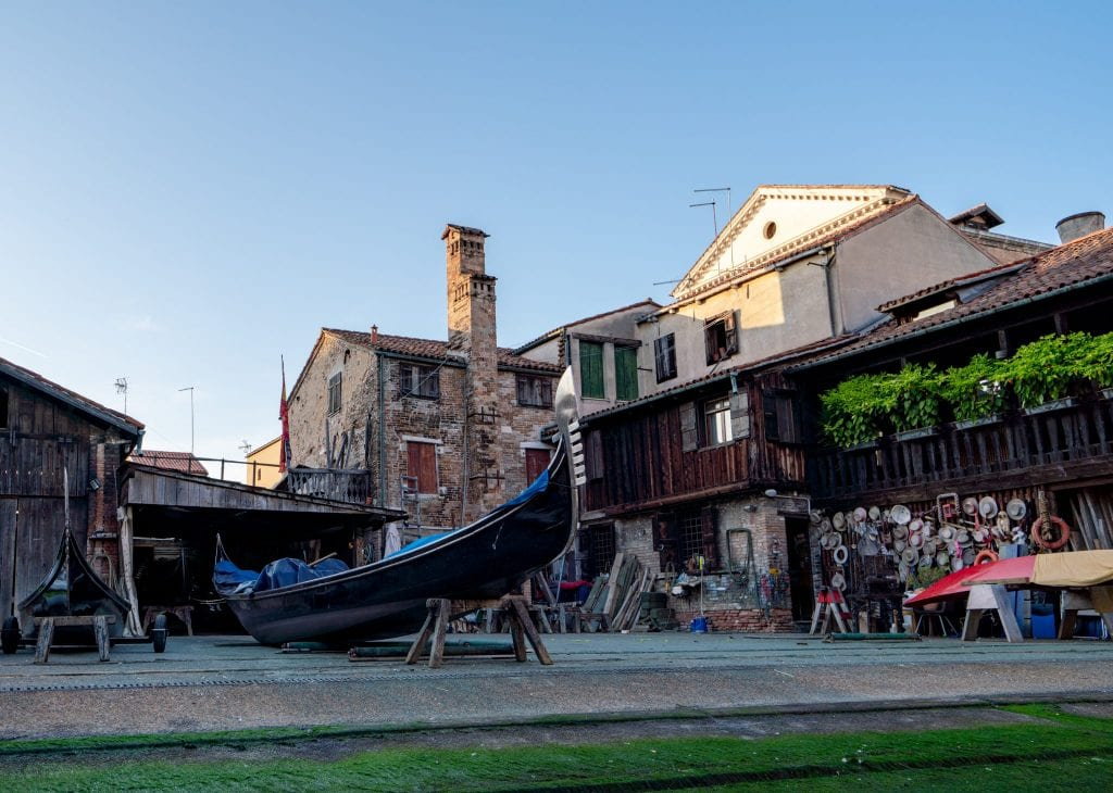 Photo of a gondola shop in Venice with a gondola on risers out front to be repaired
