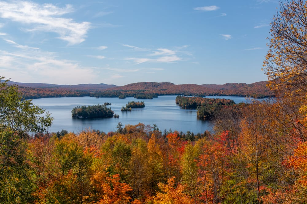 Overview in Adriondacks New York showing fall foliage and a lake in the distance. The Adriondacks are one of the best east coast USA road trips!
