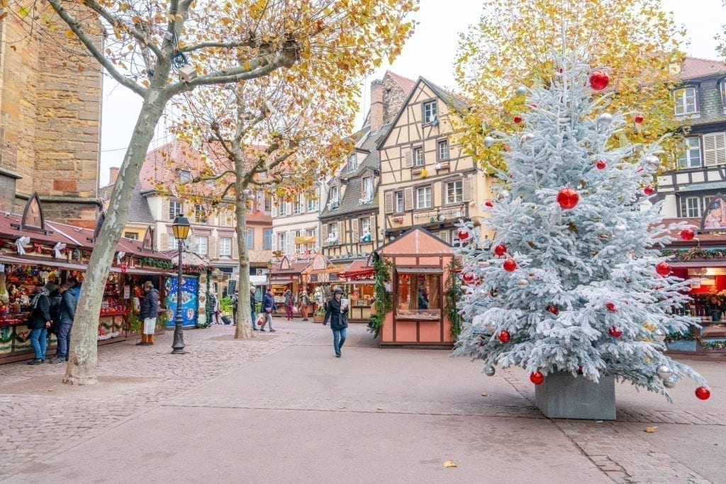 Colmar Christmas Market with white tree with red ornaments to the right
