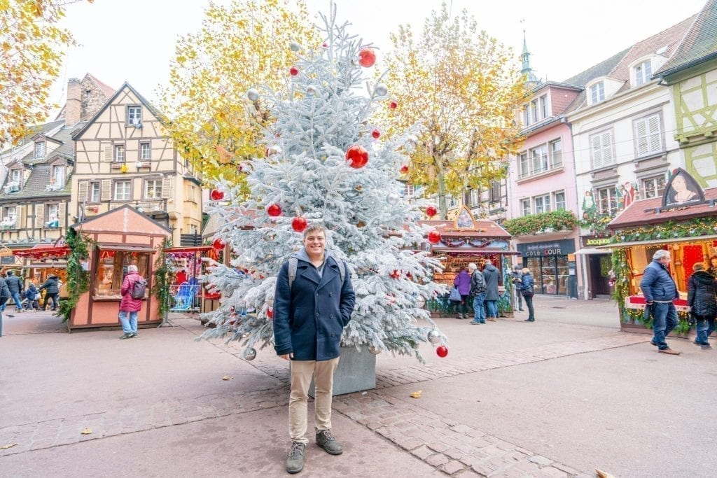 Jeremy Storm in a navy peacoat standing in front of a white Christmas tree during winter in Colmar France