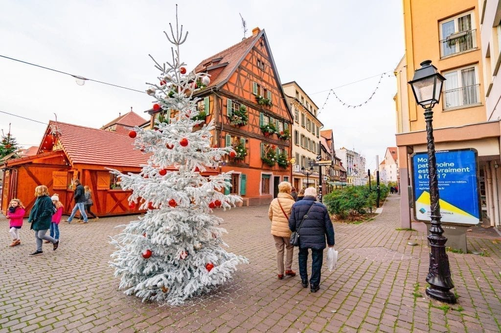 Older couple walking past a white Christmas tree in Colmar with half-timbered houses in the background