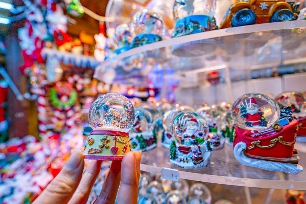 Small snow globe being held up while shopping at Colmar Christmas markets