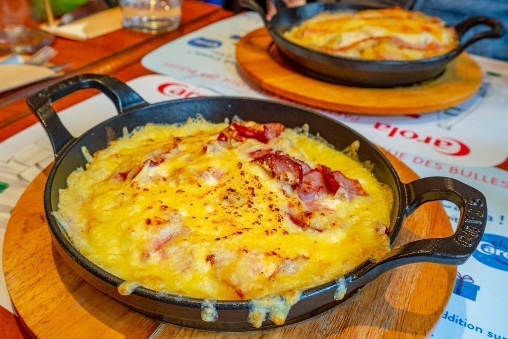 Cheesy rosti served in a round cast iron pan--this is a typical food in Alsace and deserves to be on your list of things to do in Strasbourg France!