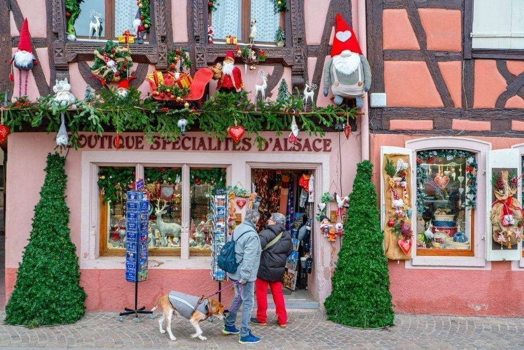 Couple shopping in front of a pink storefront in Colmar that is decoarted for Christmas in Colmar