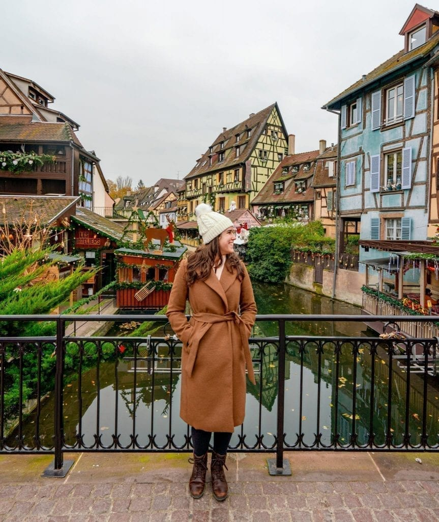 Kate Storm in a brown coat standing in front of a canal in Colmar in winter