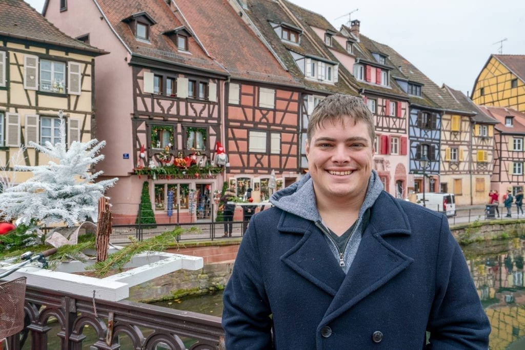 Jeremy Storm in a blue coat standing in front of colorful houses in Colmar France