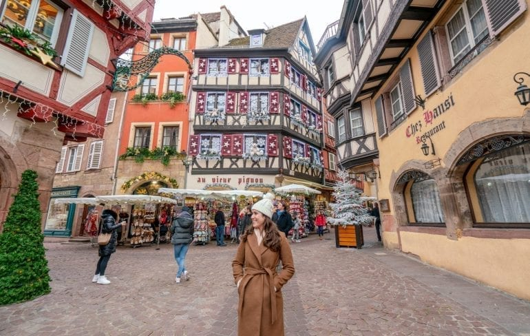 Kate Storm in a brown coat approaching the camera. Several houses decorated for Christmas in Colmar France are behind her.