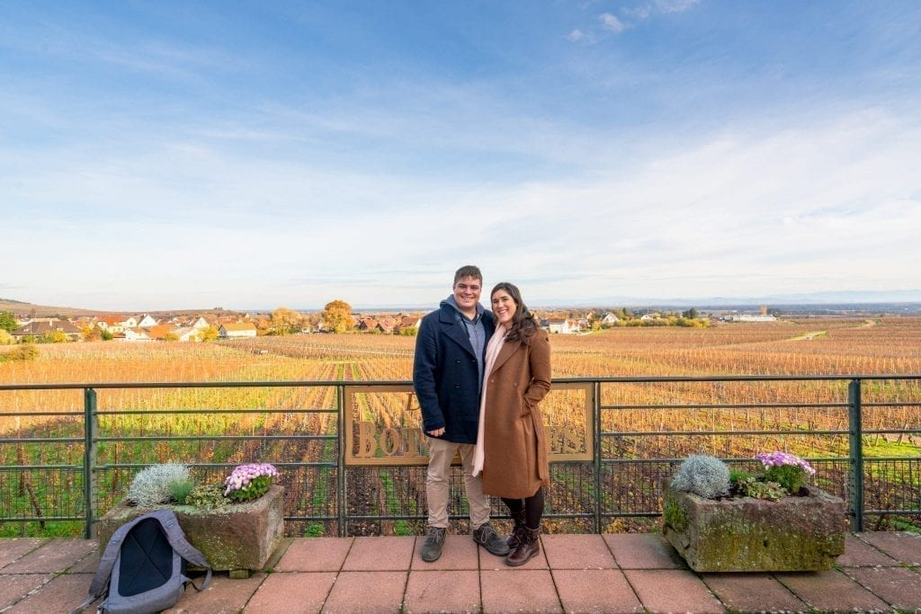 Jeremy Storm and Kate Storm at a winery on the Alsace Wine Route in the winter with grape vines visible behind them