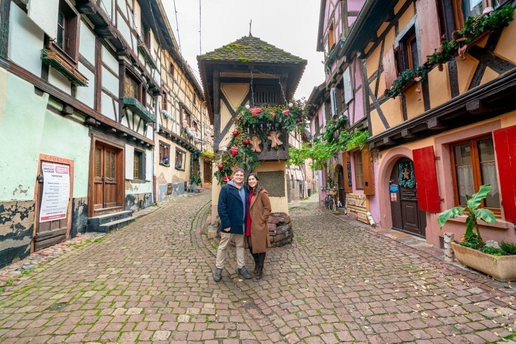 Kate Storm and Jeremy Storm wearing coats and standing in Eguisheim France surrounded by half-timbered houses