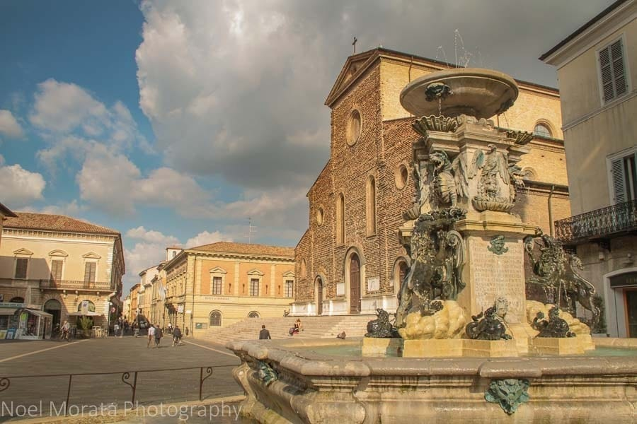 Main square of Faenza with a church and fountain visible