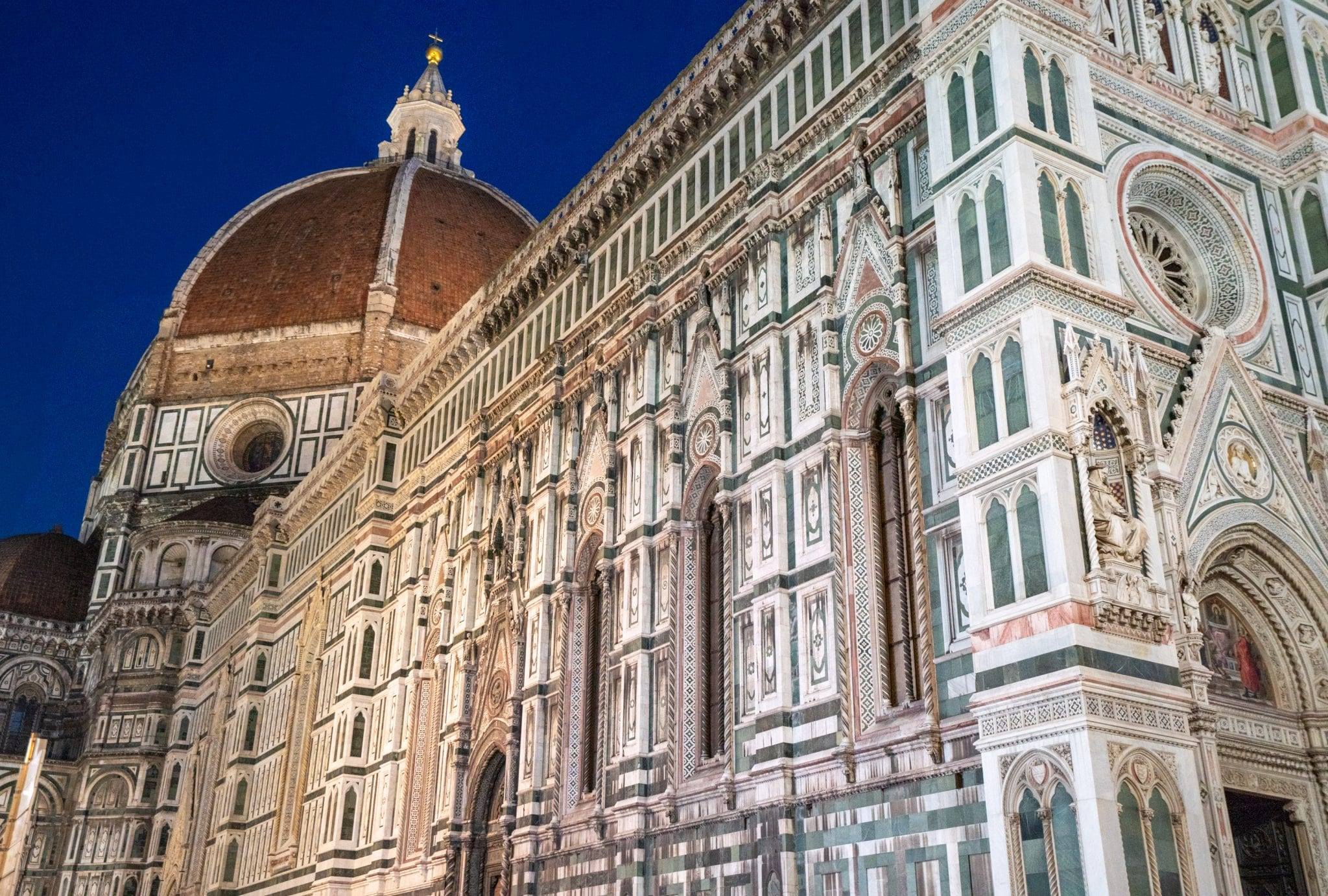 Photo of the side of Florence's Duomo at blue hour with cupola in the background. Checking out the Duomo is one of the best things to do in Florence at night