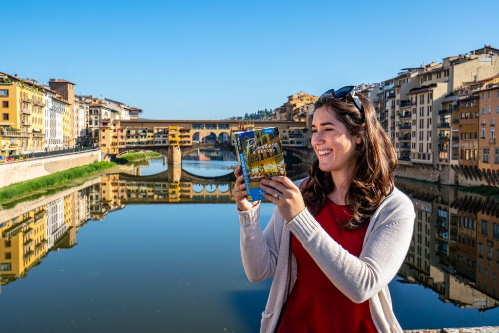 Photo of Kate Storm reading a copy of Moon Florence & Beyond with the River Arno and Ponte Vecchio in the background