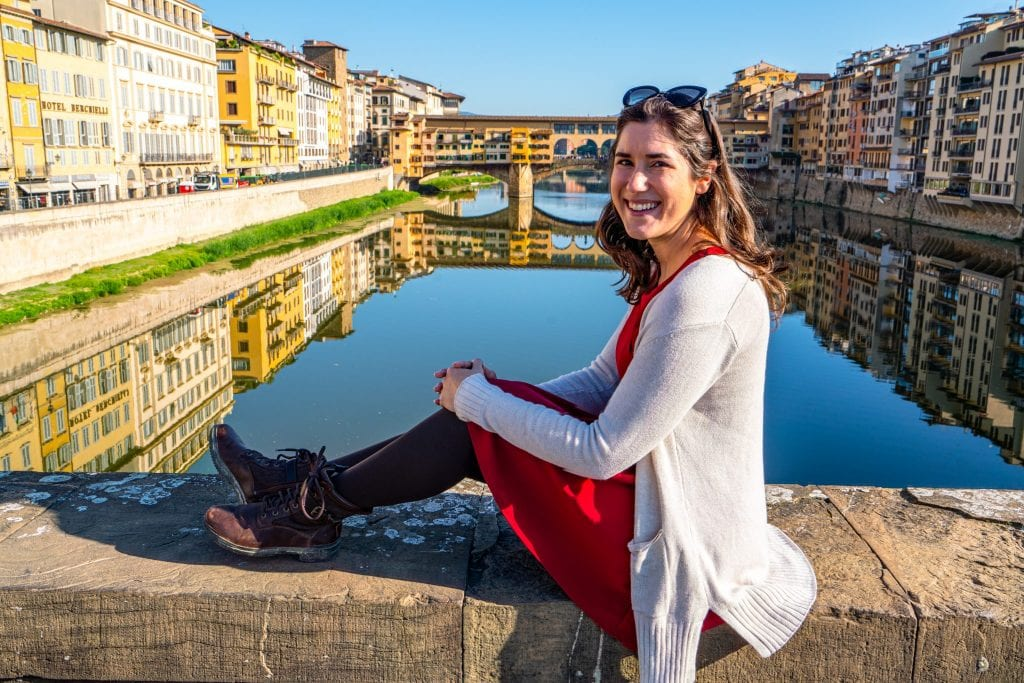 Kate Storm in a red dress sitting on a bridge overlooking the Ponte Vecchio in Florence. Florence is a fabulous place to spend 7 days in Italy!