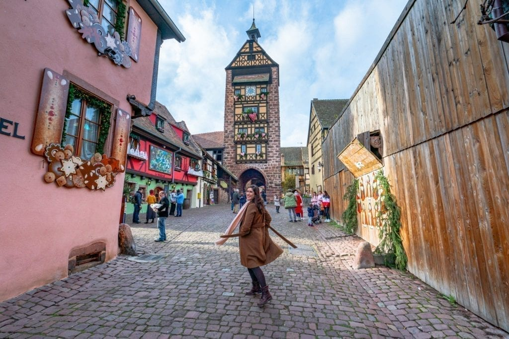 Kate Storm in a brown coat in the Alsace village of Riquewihr with a clock tower in the background