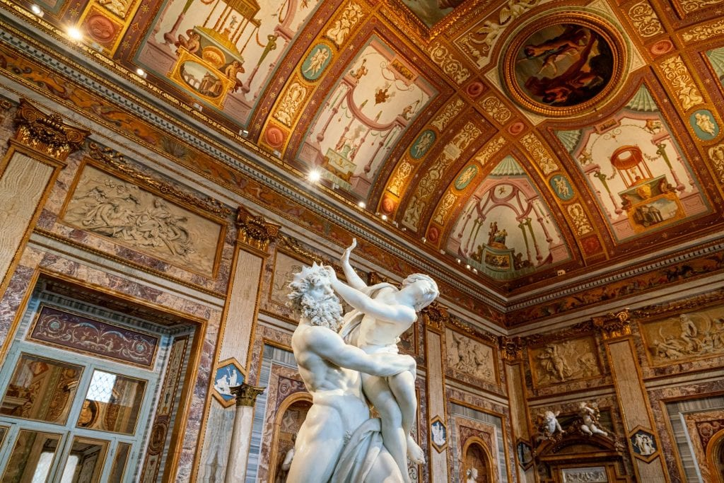 Interior of the Galleria Borghese in Rome, with a baroque statue in the center of the frame