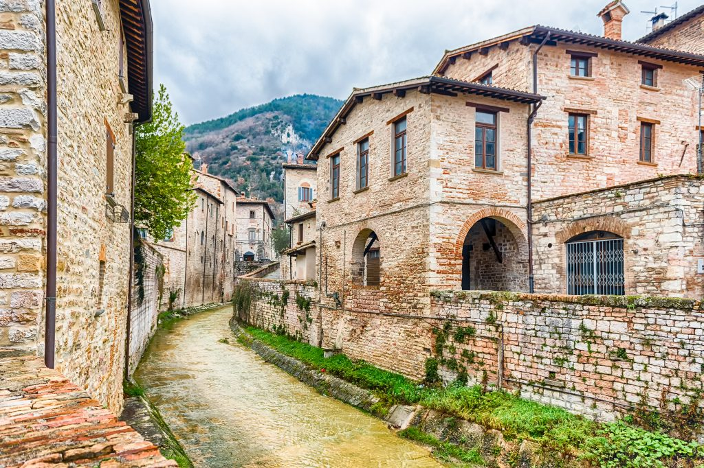 view of a river running between stone buildings in gubbio, one of the prettiest small villages in italy