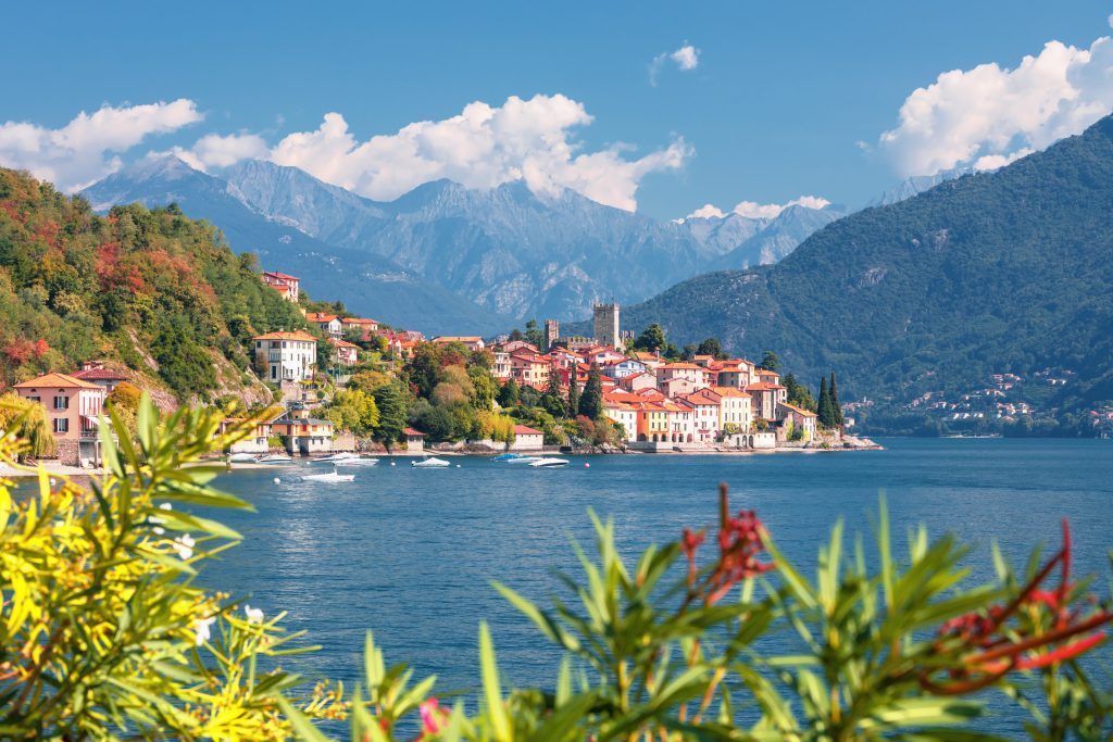 Malcesine italy as seen from across the water with greenery in the foreground and mountains behind the village
