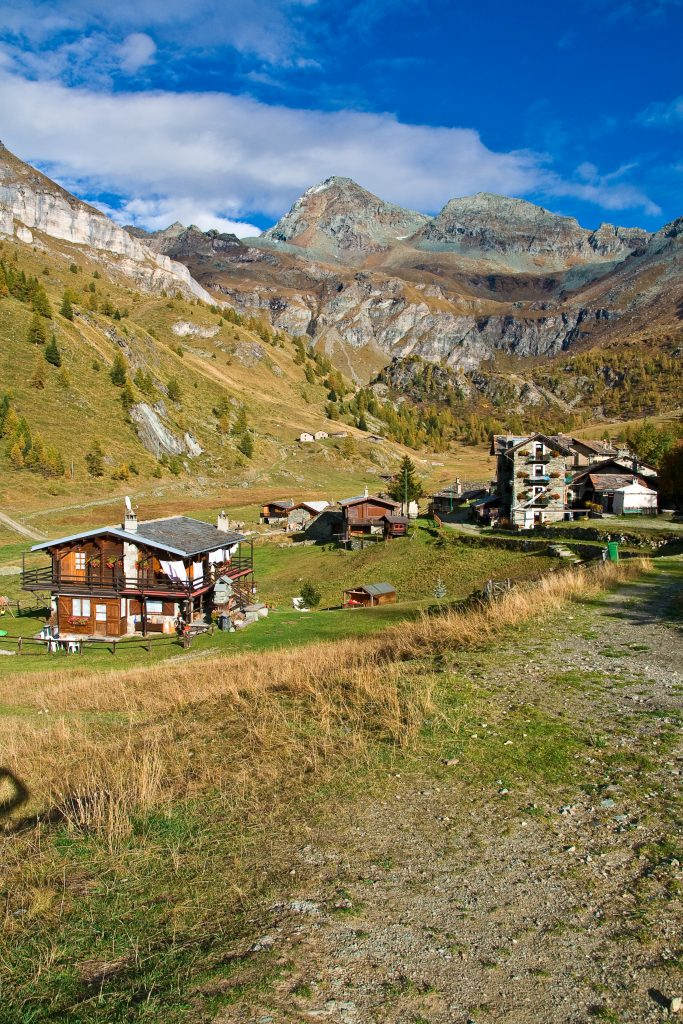 view of alpine buildings in cheneil italy with dolomites in the background