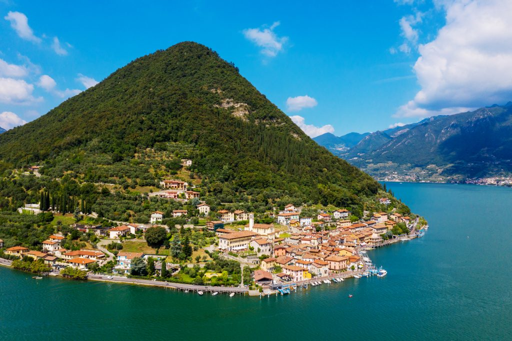 aerial view of Peschiera Maraglio with a large hill behind it and lake iseo in the foreground