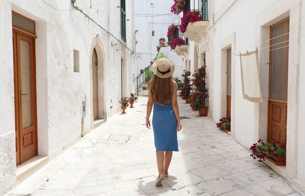 young woman in a blue dress walking along a whitewashed street in Locorotondo, one of the best italian villages to visit