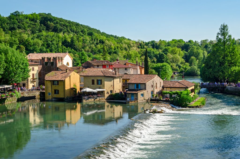 small italian village of Borghetto sul Mincio as seen from across the water, with a very small waterfall in the foreground