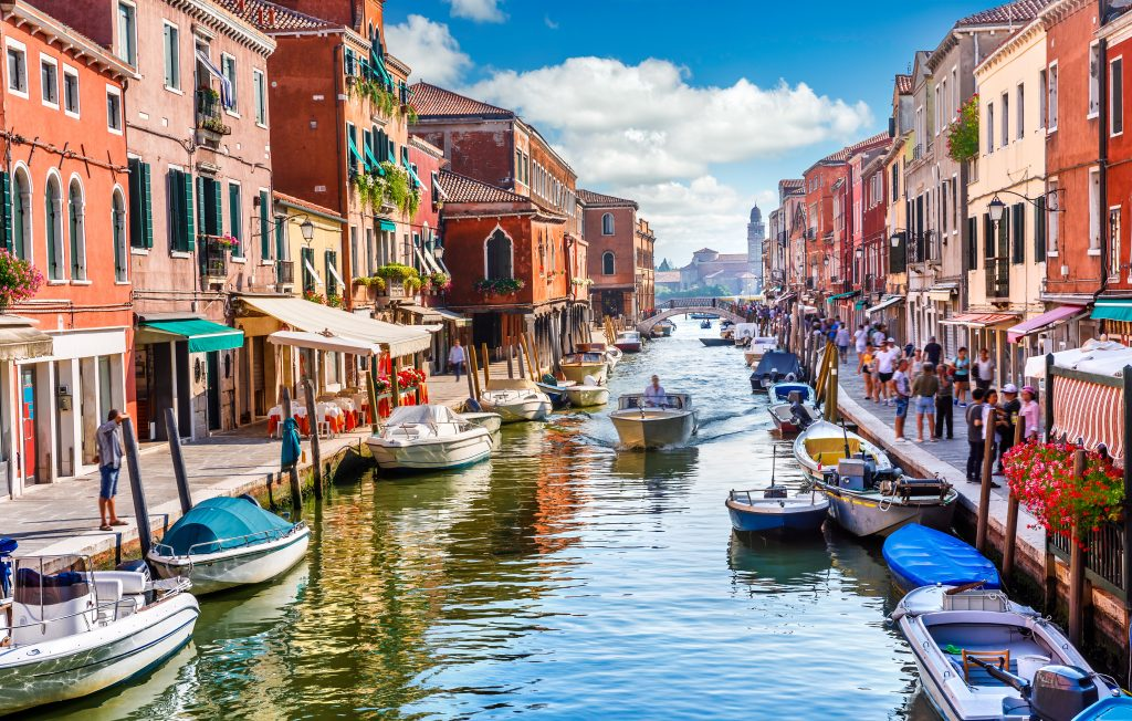 colorful buildings lining a busy canal in murano italy