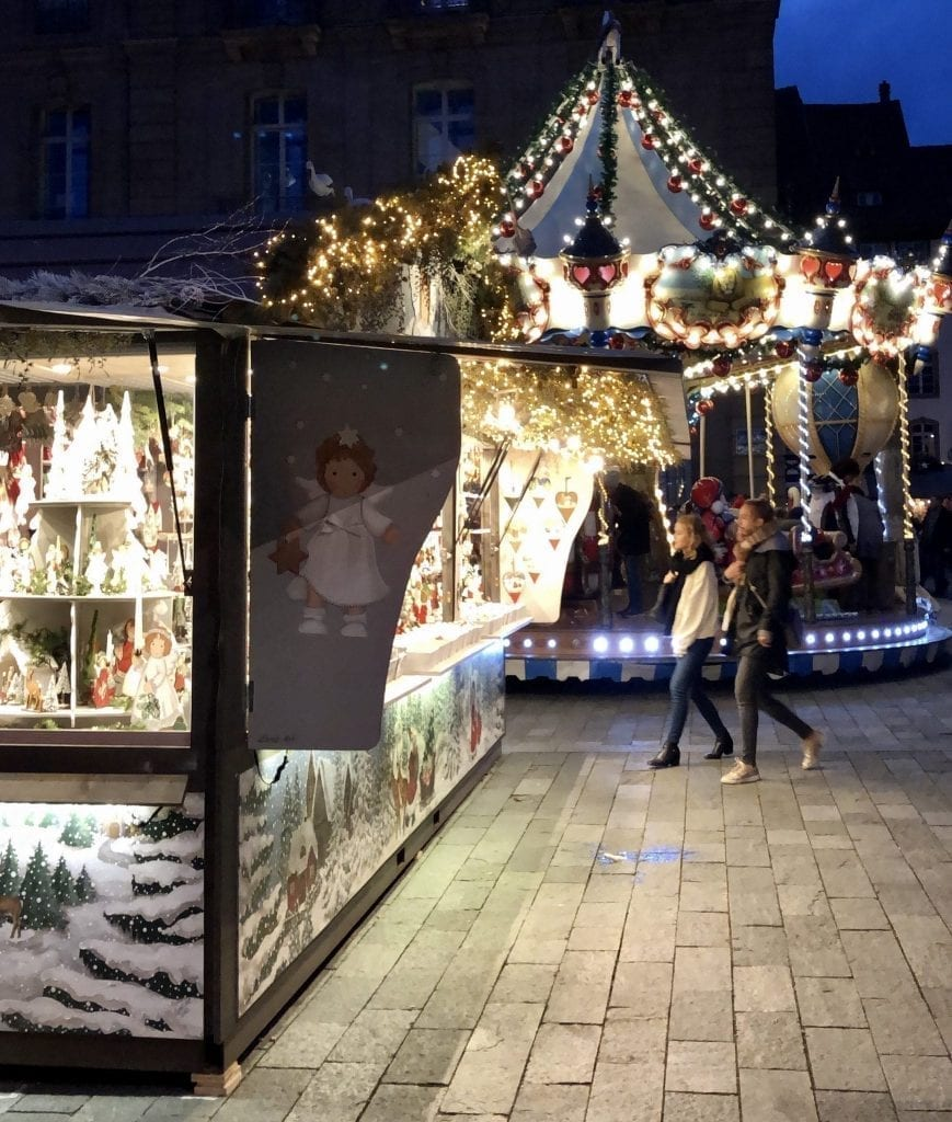 Christmas market stall with carousel and a couple walking in the background at night in Strasbourg in December