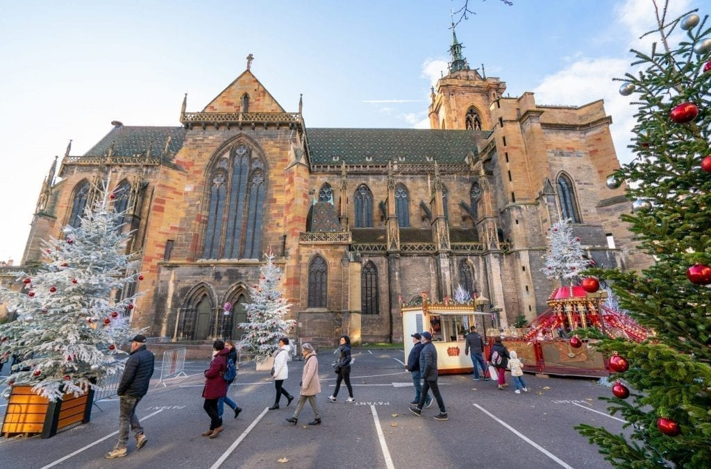 Church in Colmar in winter with Christmas trees and children's ride set up in front of it