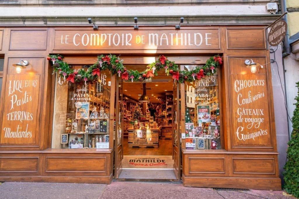 Photo of wooden Le Comptoir de Mathilde storefront in Colmar France, decorated for Christmas