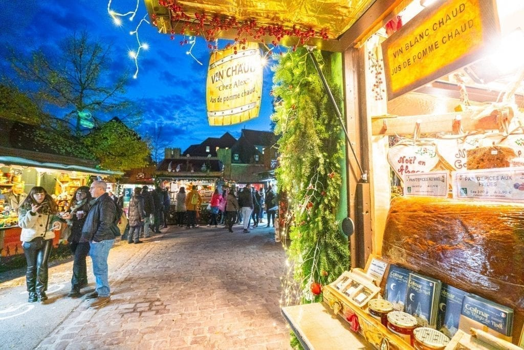 Christmas market stall open in Colmar at night with dark blue sky visible in the background