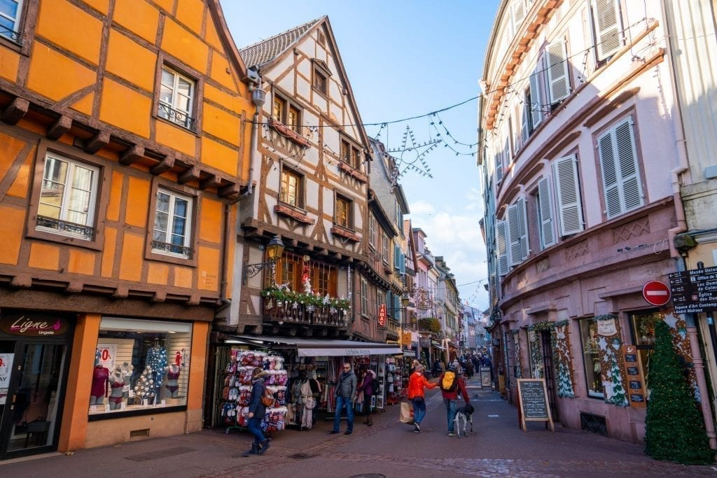 Street in Colmar France with storefronts decorated on either side for Christmas
