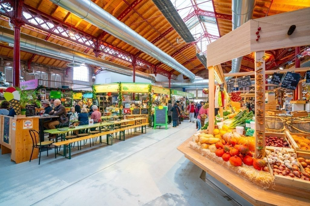 Interior of the Covered Market with fruit and vegetable stands showing. Visiting the covered market is one of the best things to do in Colmar France